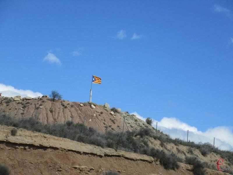 Такі прапори незалежної Каталонії майорять  на панівних вершинах вздовж дороги.