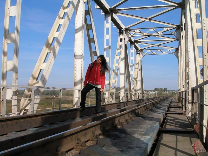 Широкі простори, внизу маленький Південний Буг, а над ним нависає залізничний міст, через який йдуть потяги у північному напрямку (на Старокостянтинів і Шепетівку).