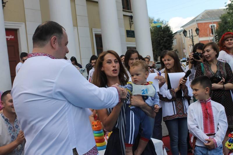 Переможець змагань малюків Гліб Чумагін з мамою та сестрою отримують подарунки від заступника міського голови Вадима Савчука
