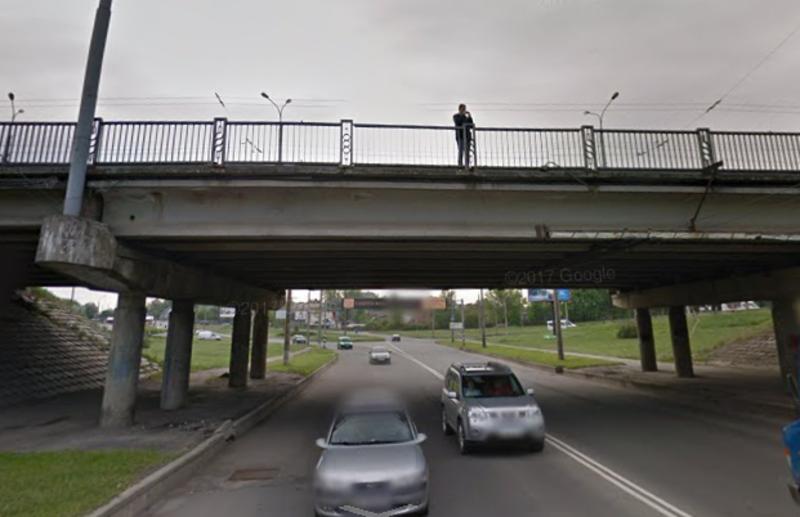 Чоловік сидів на огорожі мосту