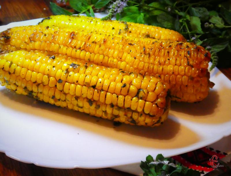 Кукурудза, запечена в духовці, виходить дуже ароматною за рахунок свіжої зелені, спецій і часнику, соковитою - завдяки маслу.