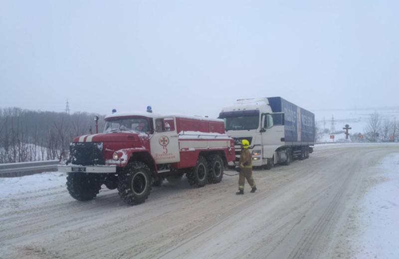 Рятувальники допомогають автівками, які опигнилися в сніжному полоні на трасах області