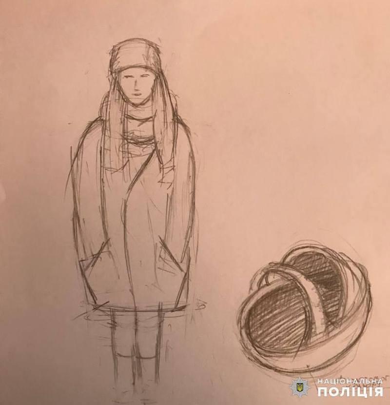 Жінка зростом близько 160 см. Мала довге русяве волосся. Була одягнена у світле пальто за коліна світлого кольору, чорну шапку та взуття на танкетці