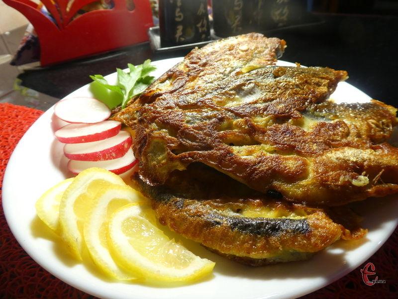 Подавати рибку в тісті з овочами та скибочкою лимона.