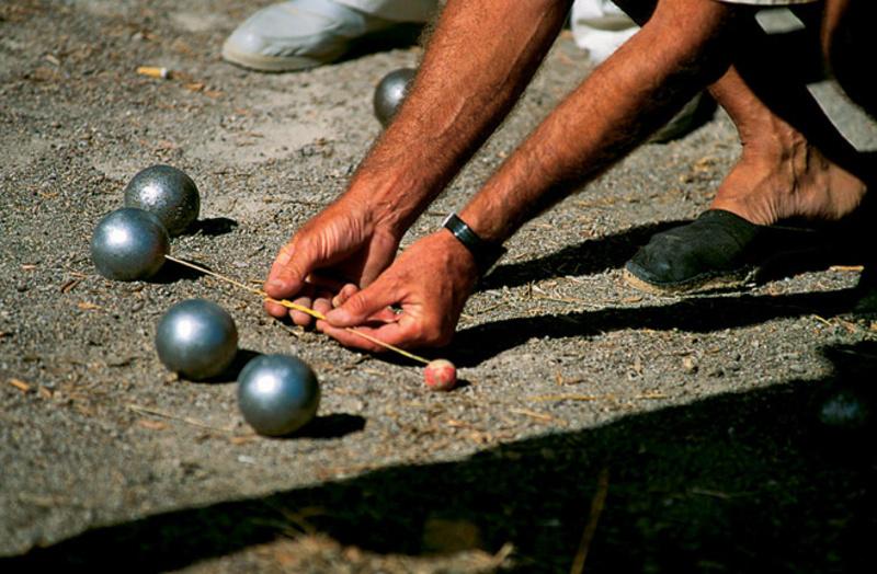 У грі петанк потрібно кинути сталеву кулю якомога ближче до червоної дерев'яної