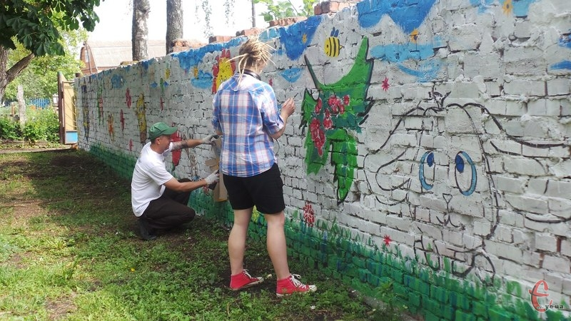 Художники розмальовують стіну