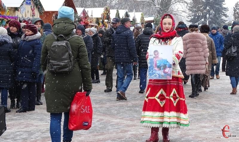 Поряд з торговими прилавками ходять зі скриньками і фотографіями дітей дівчата, одягнені у народне вбрання
